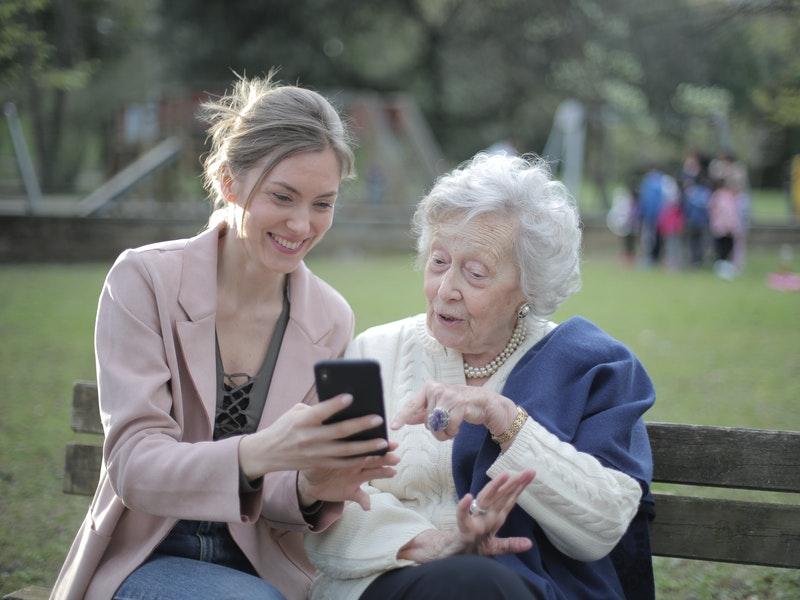 une jeune montre quelque chose sur son téléphone à une personne âgée